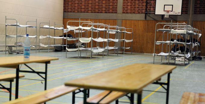 Notdürftig eingerichtete Betten und Tische für Flüchtlinge in einer Dortmunder Turnhalle.